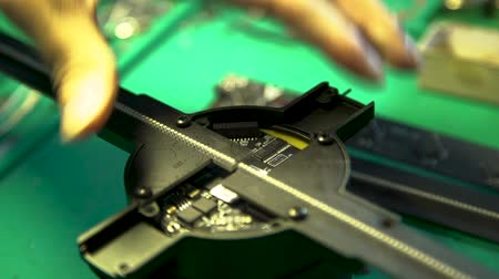 Close up of a hand fixing a small holographic fan with a screw and screwdriver