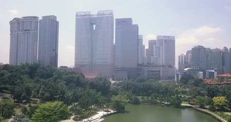 Aerial view in Malaysia, Kuala Lumpur of tall skyscrapers, buildings, and a large pond in a public park