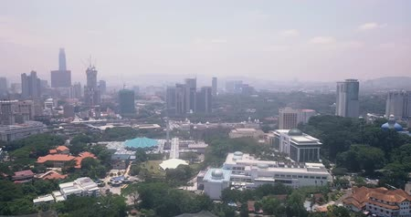 Aerial pan view of Malaysia, Kuala Lumpur of trees, forests, parks and city skyline with tall skyscrapers