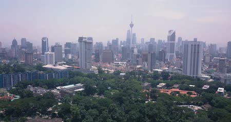 Aerial pan view of Malaysia, Kuala Lumpur of trees, parks and city skyline with tall skyscrapers