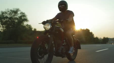 caucasiano : Young caucasian biker riding a custom built cafe racer motorcycle in the city at sunset, side view stabilized footage