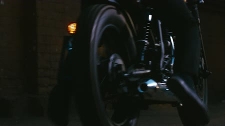 motocykl : Close-up locked down shot of a biker driving a custom built cafe racer motorcycle against a brick wall Wideo