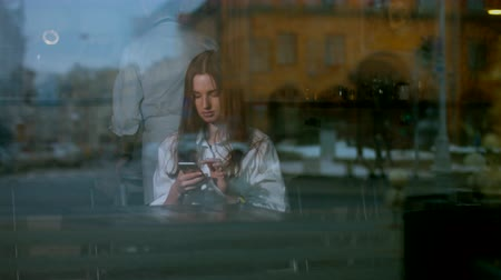 dedo : Young attractive Caucasian female using her phone. Shot through the window. 60 FPS 4K UHD Shot with Blackmagic URSA Mini