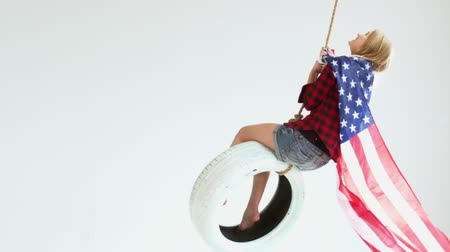четверть : Wide shot of young Caucasian girl with waving American flag riding on a tire swing against white background. 1080 HD 120 FPS Slow motion. Shot with Blackmagic URSA Mini