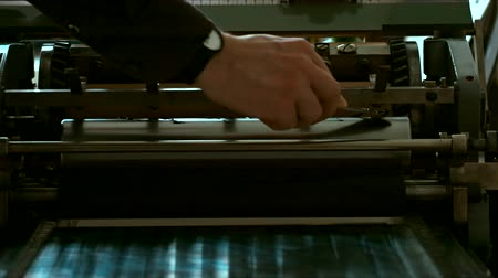 text knihy : Caucasian male putting ink on a vintage letterpress machine roll. Tracking left to right 4k 60 FPS. Shot with Blackmagic URSA Mini Dostupné videozáznamy