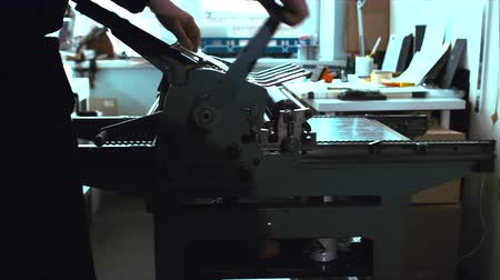 máquina de escrever : Making a print on a vintage letterpress machine. Tracking left to right 4k 60 FPS. Shot with Blackmagic URSA Mini Stock Footage