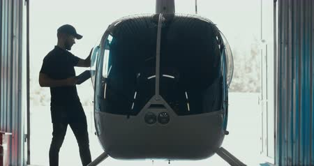 aeroespaço : Male mechanic in uniform examining helicopter. Pre flight inspection at the airport. 4K UHD Vídeos