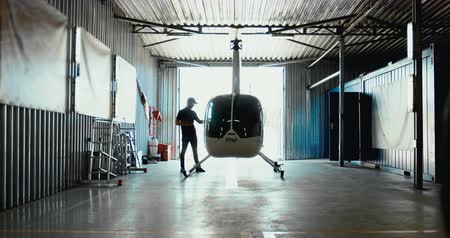 denetleme : Male mechanic in uniform examining helicopter. Pre flight inspection at the airport. 4K UHD Stok Video