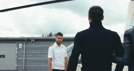 kaptan : TRACKING commercial pilot in uniform greeting clients near small private helicopter on a landing point. 4K UHD Stok Video