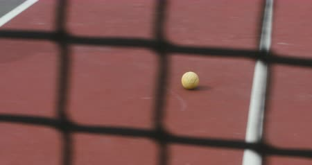 single shot : DOLLY CU shot of tennis ball rolling on a surface of an outdoor tennis hardcourt. 4K UHD