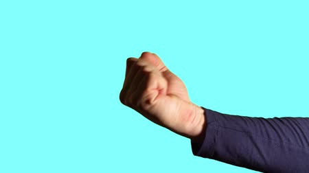 forefinger : Close-up hand gesture - fist sign. Male hand shows fist, threatening and warning on blue background.