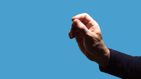 forefinger : A close-up hand gesture is a religious sign. Male hand making gesture - Christian cross on a blue background.