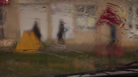 meteoroloji : While the car was moving, a drop of water was falling on the glass of the car, and it was raining outside. In the background you can see the building and the playground. Stok Video