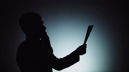 contorno : Silhouette of a man. The shadow of a man on a light background. The man is not satisfied with the report received and asks for a remake. Emotions, failure, dissatisfaction.