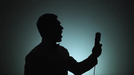 odstín : Silhouette of a man. The shadow of a man on a light background. The man is singingin a microphone. Emotions, song. Slow motion.