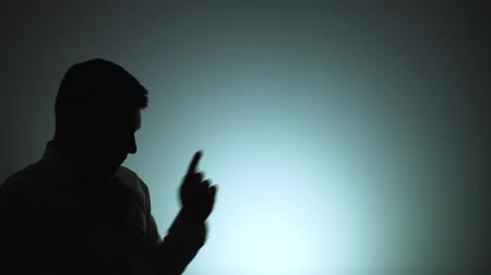 contornos : Silhouette of a man. The shadow of a man on a light background. The man is dancing actively playing with index fingers. Emotions, dance. Slow motion Vídeos