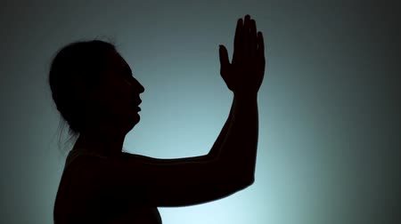 contornos : Silhouette of a woman. The shadow of a woman on a light background. A woman prays to God, folding his arms and stretching them up. Emotions, prayer, religion, faith. Slow motion.