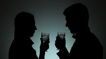bond : Silhouettes of man and woman. Shadows of men and women on a light background. A man and a woman raise glasses, say a toast, drink. Emotions, marriage, relationships.
