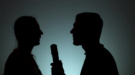 contornos : Silhouettes of man and woman. Shadows of men and women on a light background. A man and a woman sing together in a microphone. Emotions, someplace rest, singing.