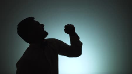 improvised : Silhouette of a man. The shadow of a man on a light background. The man is singing in an improvised microphone. Emotions, song. Slow motion.