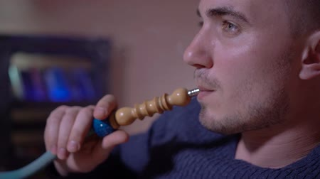 книжный шкаф : A young guy smokes a hookah, exhales smoke. Hookah smoke. Young man in smoke close up. A young guy smokes a hookah on the background of the bookcase.