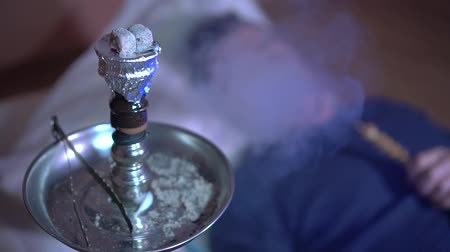 vaper : Close-up of a hookah bowl with burning coals. A young guy smokes a hookah, exhales smoke. Hookah smoke. On a plan, a young guy smokes a hookah.