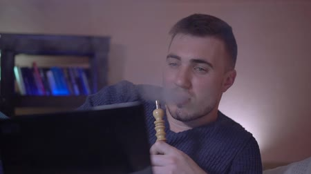 vaper : The young guy smokes a hookah, exhales smoke and works at a laptop. A young man in the smoke. A young guy on a pillow against a background of a bookcase and works at a laptop.