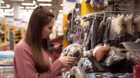dönt : A young woman chooses a pillow for a car in a supermarket, a beautiful wife buys a pillow for a car, a girl in a supermarket.