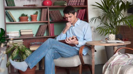книжный шкаф : A young man reads a book while sitting in the home library, a man in a blue shirt and jeans holds a book and reads, having time on the background of bookshelves in the library.