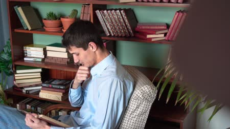 книжный шкаф : A young man reads a book while sitting in the home library, a man in a blue shirt and jeans holds a book and reads, having time on the background of bookshelves in the library. Side view.