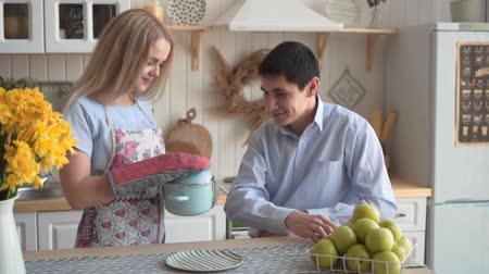 szál : Young and happy couple in the kitchen. Happy couple in the kitchen. A young woman cooked dinner and her boyfriend sniffs what she cooked, he likes it. Stock mozgókép