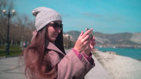 atracação : A young girl with long hair in glasses, a hat and a coat on the embankment in spring. A girl is holding a phone and making a photo on the background of the sea.