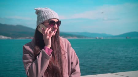 mooring : Young girl with long hair in glasses, hat and coat on the embankment in the spring. The girl is talking on the phone on the background of the sea.