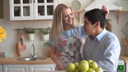 kötény : Young and happy couple in the kitchen. Happy couple in the kitchen. A young woman hugs and strokes her boyfriend, they smile and talk. Stock mozgókép