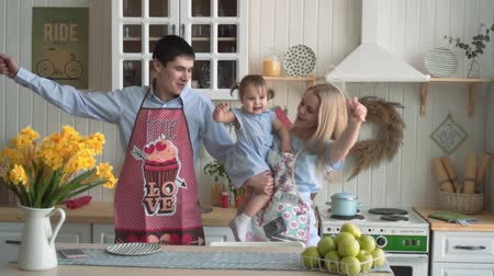 bliskosc : Happy family in the kitchen, where mom is holding her daughter. Mom and Dad sing into fictional microphones and dance, everyone laughs and smiles. Smiles, hugs, happy family. Wideo