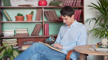 книжный шкаф : A young man reads a book while sitting in the home library, a man in a blue shirt and jeans holds a book and reads, having time on the background of bookshelves in the library. Medium plan.