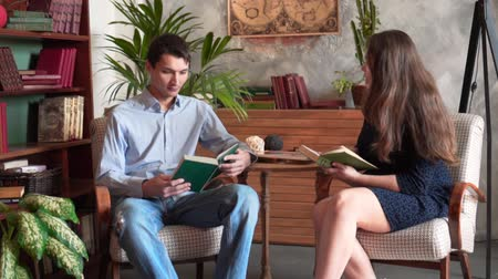 kabine : The guy and the girl are reading books while sitting in the home library, a man in a blue shirt and jeans, a girl in a dark dress. The girl shows the guy the text of the book.