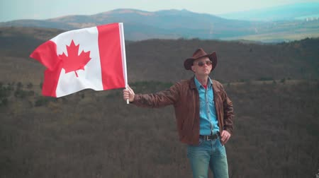 frizura : A man in a hat and sunglasses, leather jacket and jeans holding a Canadian flag on the background of mountains, woods and the sky. Flag of Canada develops in the wind.