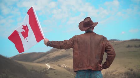 головной убор : A man in a hat and sunglasses, a leather jacket and jeans holding a Canadian flag against the backdrop of mountains, forests and the sky. A man stands with his back in the frame.