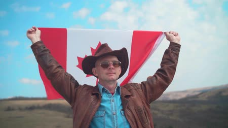 ulus : A man in a hat and sunglasses, leather jacket and jeans holding a Canadian flag over his head on the background of mountains, woods and the sky. Flag of Canada develops in the wind. Stok Video