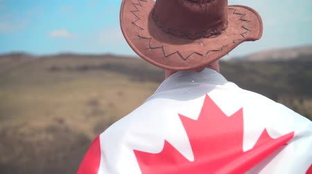 frizura : A man in a hat and sunglasses, a leather jacket and jeans threw a Canadian flag on his back against the backdrop of mountains, forests and sky. A man stands with his back in the frame.