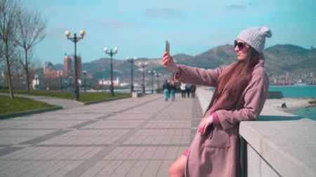 hajló : Young girl with long hair in glasses, hat and coat on the embankment in the spring. A girl takes a selfie on the phone leaning on a concrete fence on the background of the port city.