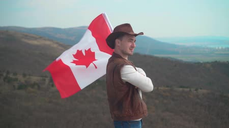 головной убор : A man in a hat, vest and leather jacket and jeans is holding a Canadian flag against the backdrop of mountains, woods and the sky. Flag of Canada develops in the wind. Стоковые видеозаписи