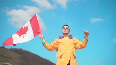 canadian maple leaf : A young man in a yellow jacket, blue jeans and glasses stands in the mountains, holds the flag of Canada and shows a victory sign. Behind the backdrop of the mountains and the sky.