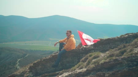 canadian maple leaf : A young man in a yellow jacket, blue jeans and glasses sits on a ridge, followed by the flag of Canada. Background of mountains and sky. Flag of Canada develops in the wind.