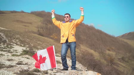 alkollü içkiler : A man in a yellow jacket, blue jeans and glasses stands on a mountain and shows victory, the flag of Canada is set in the ground. Background of mountains and sky. Flag of Canada develops in the wind.