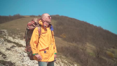 tramp : A man in a yellow jacket, glasses and a large tourist backpack stands in the mountains, enjoying the scenery. In the background are hills and sky. Mountain landscape.