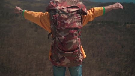 landloper : A man in a yellow jacket, glasses and a large tourist backpack stands in the mountains, raises his hands up, a symbol of freedom. A man stands with his back in the frame.