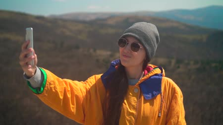 realizar : A young girl with long dark hair in a yellow jacket, a gray cap and glasses stands on a mountain and takes a selfie on the phone. Background mountains, sky.
