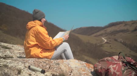 magasság : A young girl with long dark hair in a yellow jacket and a gray cap sits in the mountains and looks at a tourist map. Background mountains, sky.